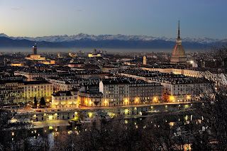 The beautiful city of Turin at dusk with the unmistakable Mole  Antonelliana to the right and the alpine peaks in the distance