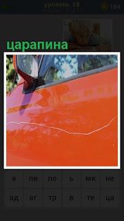 на красной поверхности автомобиля имеется длинная царапина