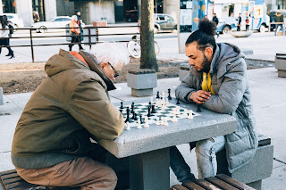 A young caregiver plays chess with a senior outside in winter.