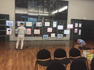 Een medewerker hangt de winnende tekeningen op.