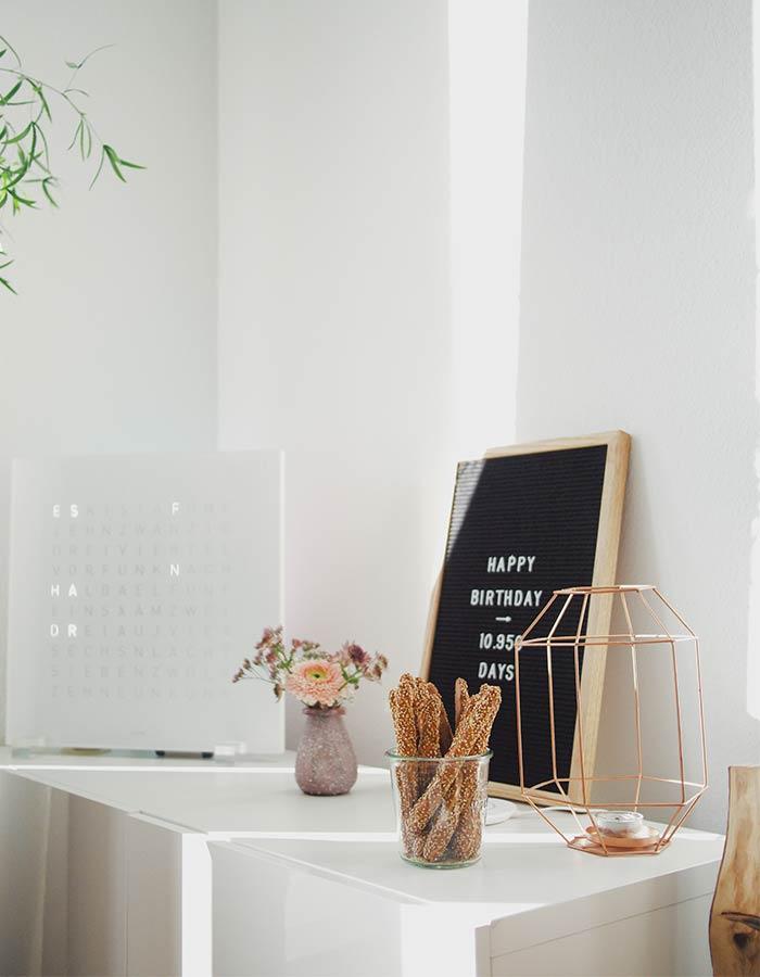Decorando a cômoda do quarto com quadros, vela em castiçal geométrico rose gold e flores, com inspiração minimalista.
