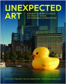 Cover of Unexpected Art, featuring an enormous, bright yellow rubber duck floating in a blue-green body of water with brick and steel buildings behind it.