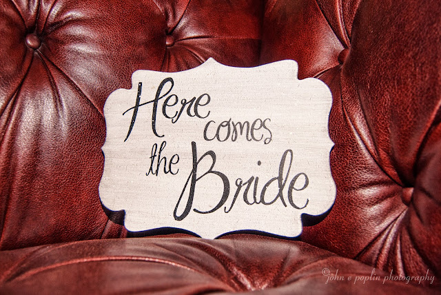 A here Here comes the Bride sign sits on a burgundy leather couch for a wedding in Golden Colorado