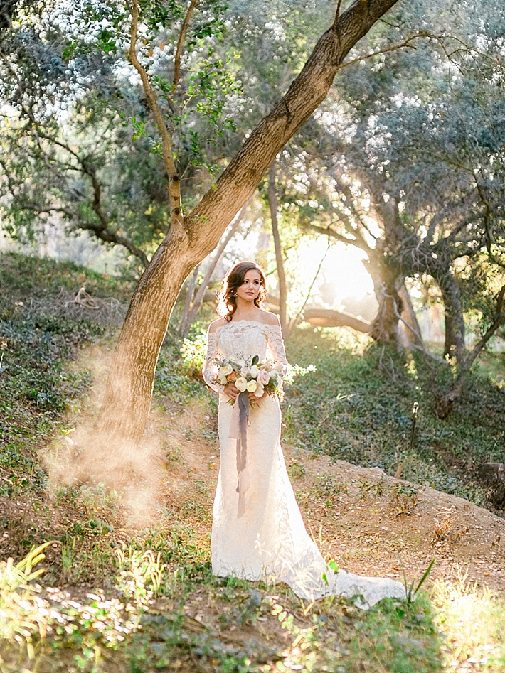 Bride in off the shoulder lace wedding dress with sun shining behind her | Photo by Dennis Roy Coronel | See more on thesocalbride.com