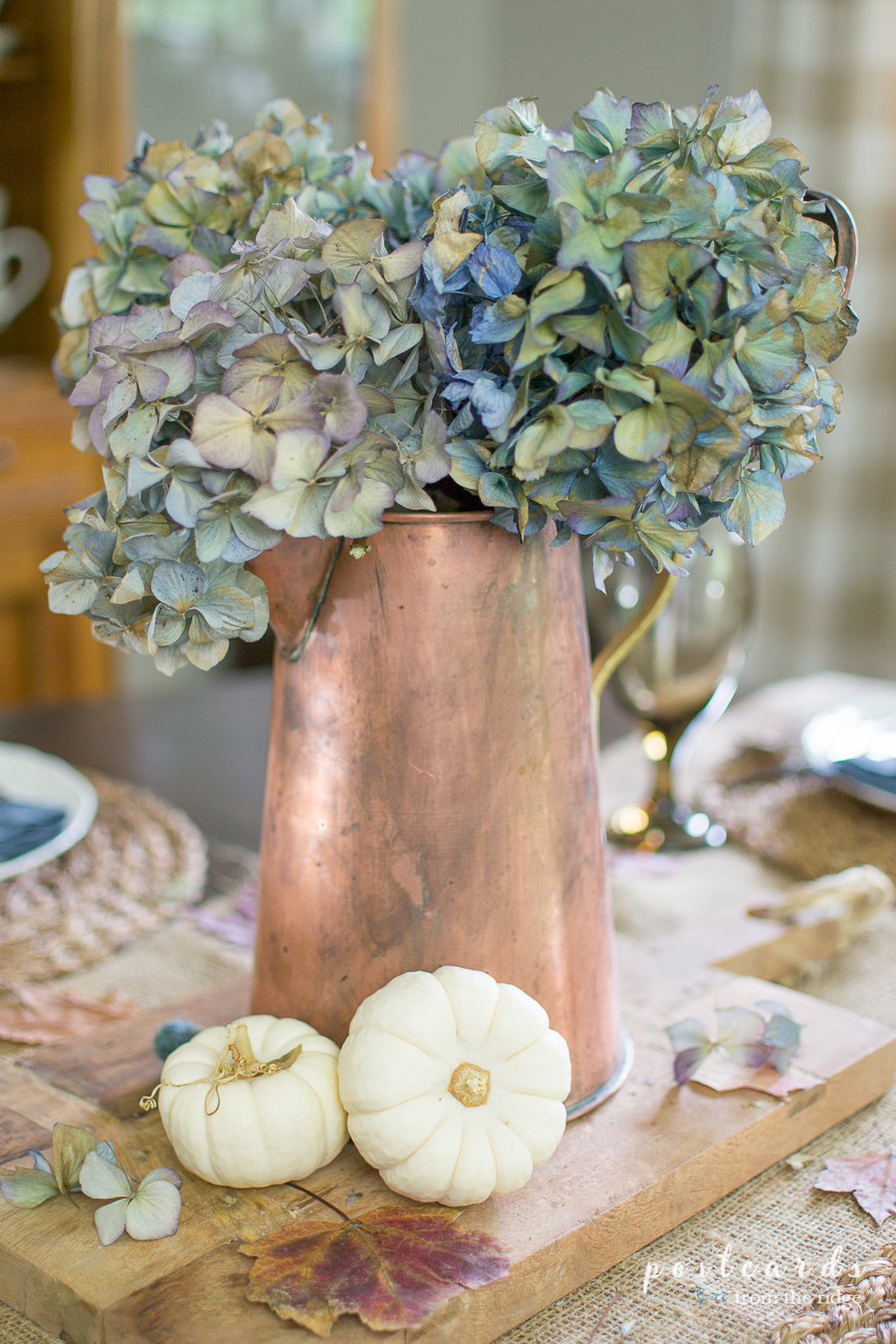 copper pitcher with blue dried hydrangeas and small white pumpkins