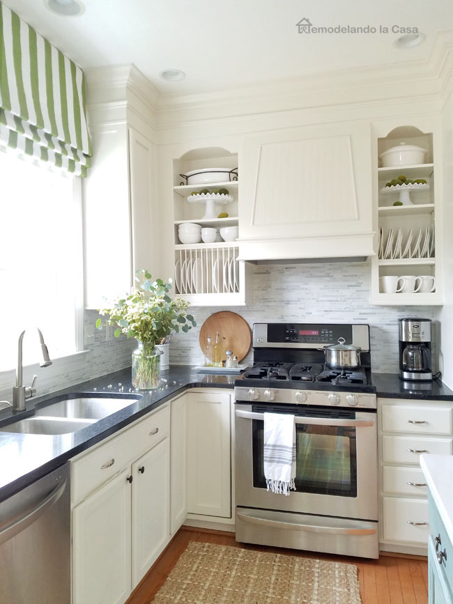 white farmhouse kitchen with green roman shade and blue kitchen island.