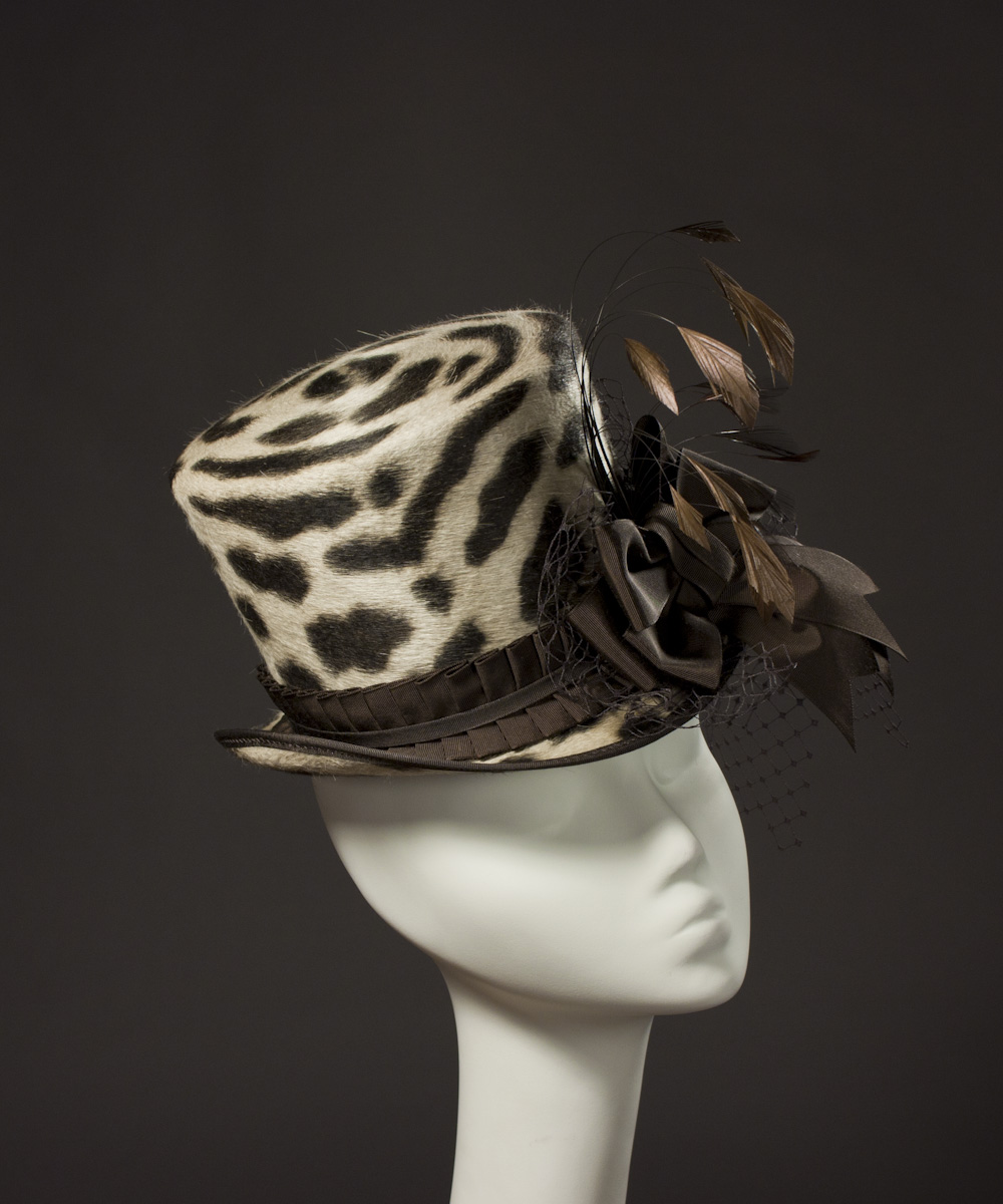 ae1e612e40e0 The leopard print 'Wellington' top hat is trimmed with chocolate brown  vintage ribbon, veiling, and stripped coque feathers that bounce and shimmy  as you ...