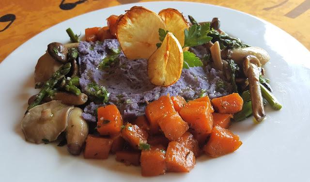 Parmentier de patata violeta, con boniato confitado, revuelto de setas y espárragos verdes, y chips de yuca.