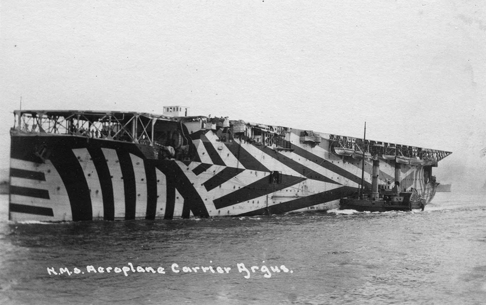 El portaaviones británico HMS Argus. Convertido de un transatlántico, el Argus podía llevar entre 15 y 18 aviones. Comisionado al final de la Primera Guerra Mundial, el Argus no vio ningún combate. El casco del barco está pintado en camuflaje Dazzle. El camuflaje deslumbrante se usó ampliamente durante los años de guerra, diseñado para dificultar que un enemigo calcule el alcance, el rumbo o la velocidad de una nave, y lo convierta en un objetivo más difícil, especialmente como se ve desde el periscopio de un submarino.