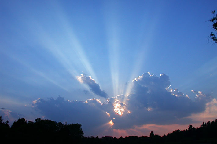 Crepuscular rays appear to converge on the sun.
