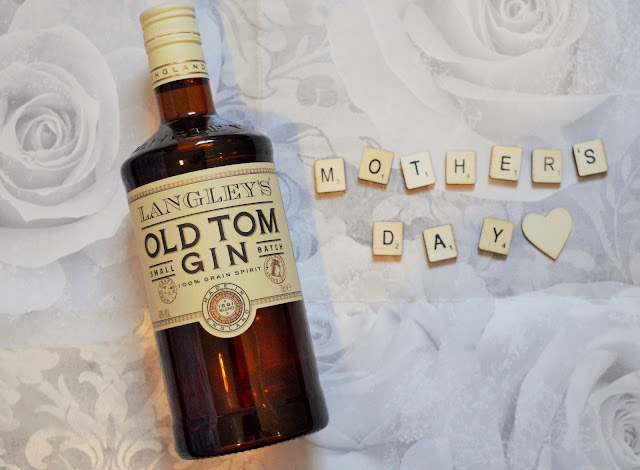 A large bottle of Old Tom Gin with Mother's Day in scrabble tiles beside it.