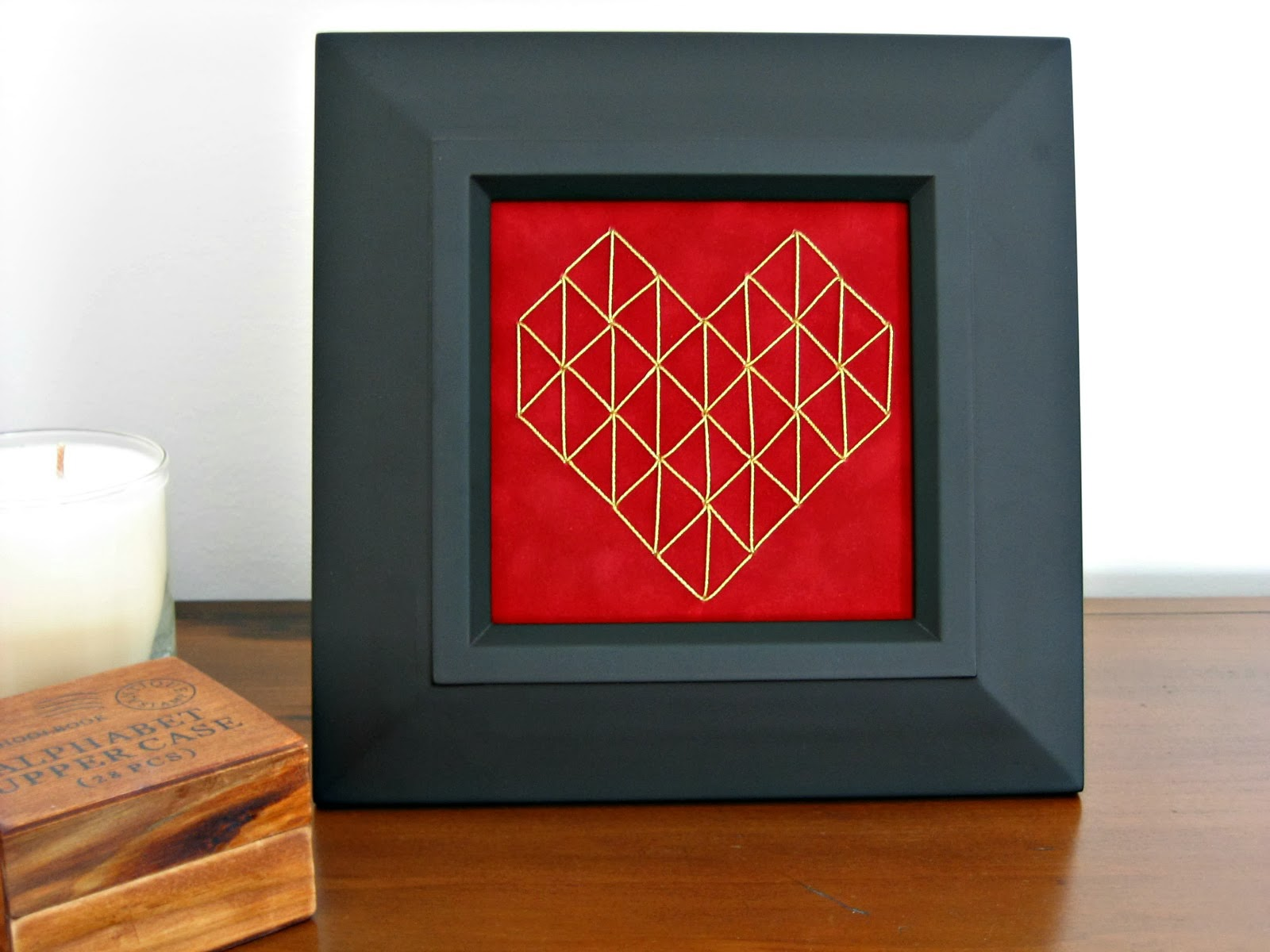 stitched geometric heart on paper in frame