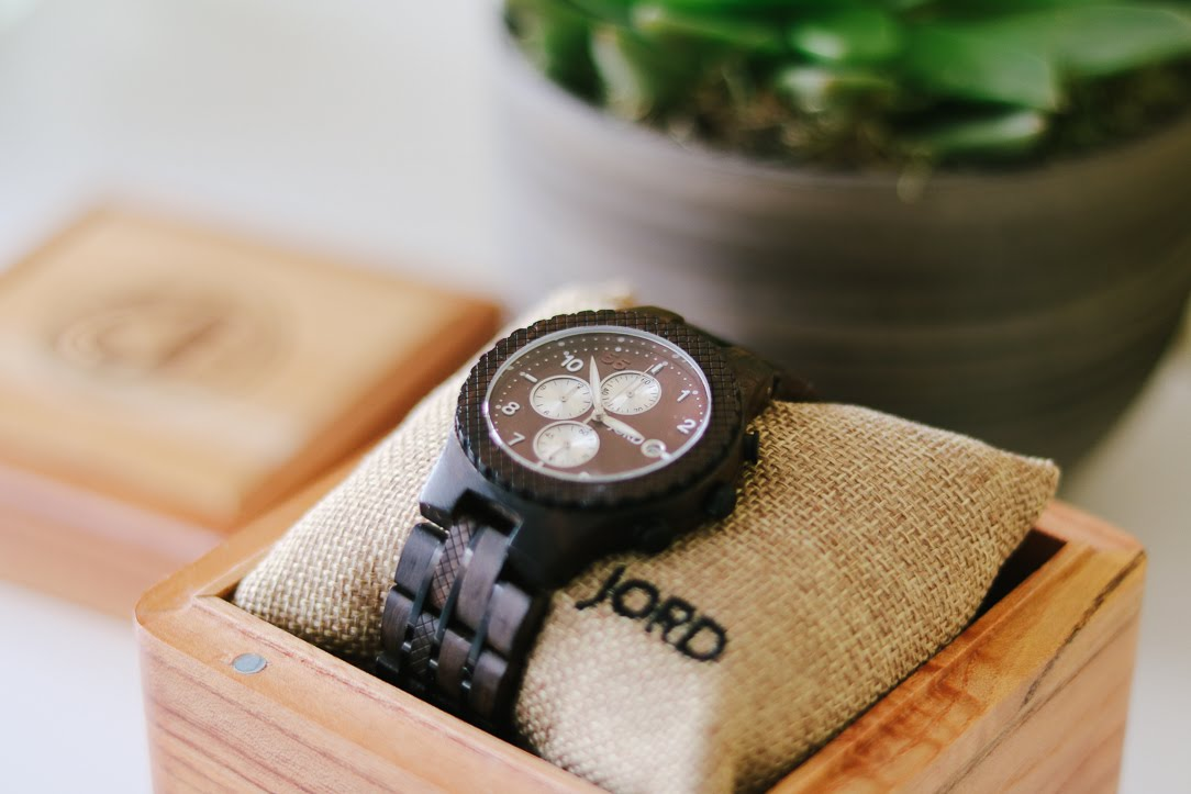 a close up of a dark wooden watch sitting in a wooden presentation case. there is a succulent in the background