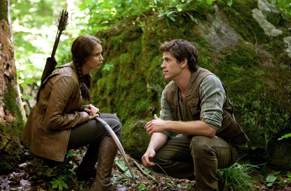 Jennifer Lawrence as Katniss Everdeen on a tree stump in wooded area facing Liam Hemsworth as Gale Hawthorne, leaves and moss all around them