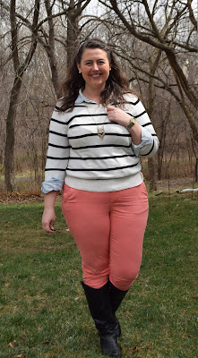 an outfit with coral chinos, a chambray layered under a striped sweater, and black boots