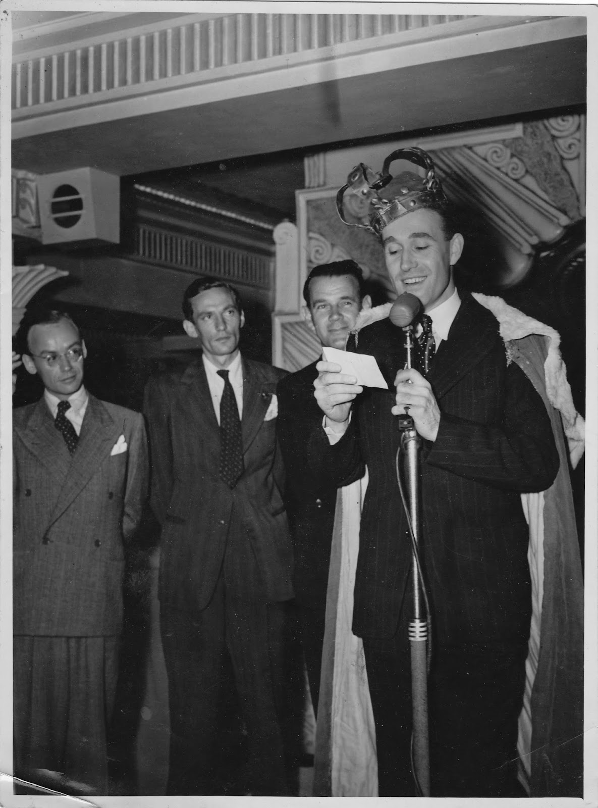 Max Oldaker, winner of the Popular Man contest, with his badly-fitting crown on 31 October 1945. Also in the photo, Jack Cazabon, Peter Finch and Jack Burgess