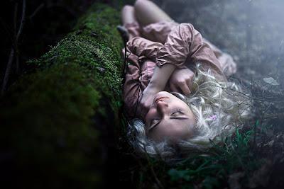 Linda chica con pelo blanco acostada en el césped junto a un arbol