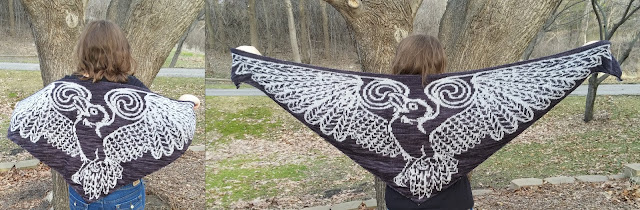 a person facing trees and grass, spreading their arms out to show a white and black shawl patterned like a bird with outspread wings