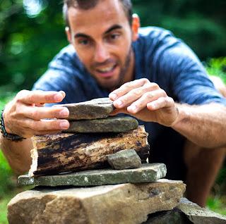 Image of a smiling man balancing rocks outdoors.