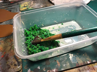 Using a brush to mix foliage and PVA glue together