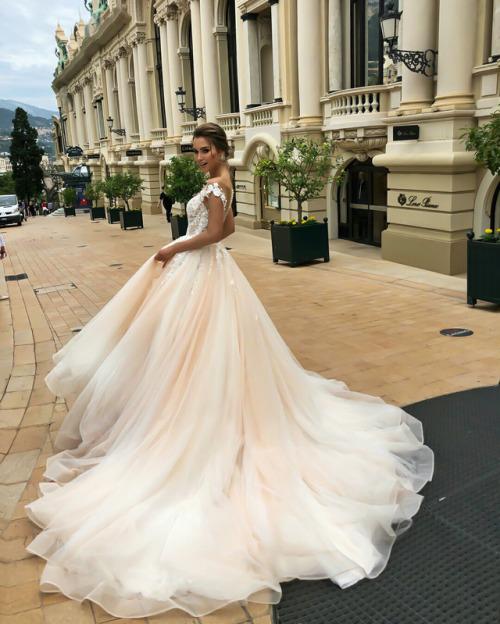 linda jovem com um vestido longo, em frente a um prédio que parece um teatro ou uma igreja antiga.