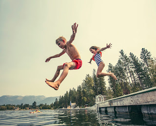 Photo of happy kids leaping into a lake