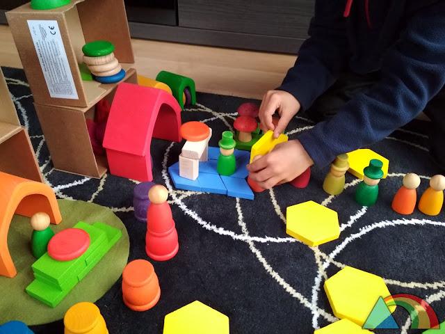 Niño jugando con nins de Joguines Grapat y casitas de Grimms Wooden Toys