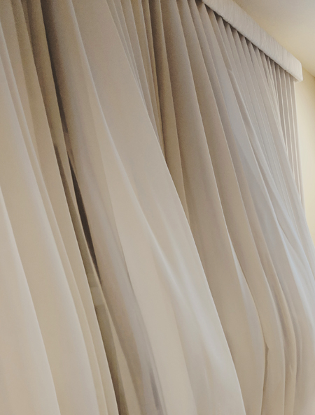 image of sheer white curtains caught in a breeze, swelling out into the living room full of air