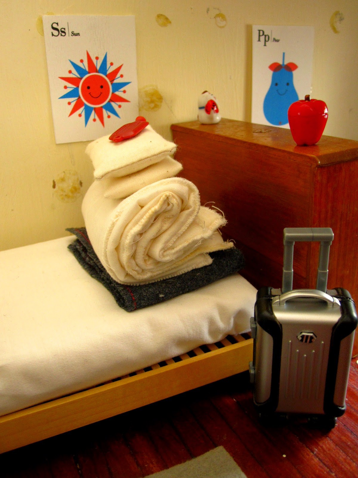 Miniature bed, stripped, with bedding folded into a pile. A rolling suitcase stands on the floor at the end of the bed.