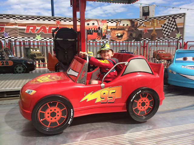 Little boy sitting in a red car on a fairground ride