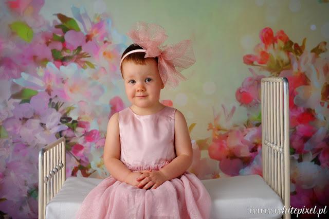 fotograf dziecięcy małych dzieci w studio, dziewczynka na sesji w slicznej sukience pozuje mała modelka