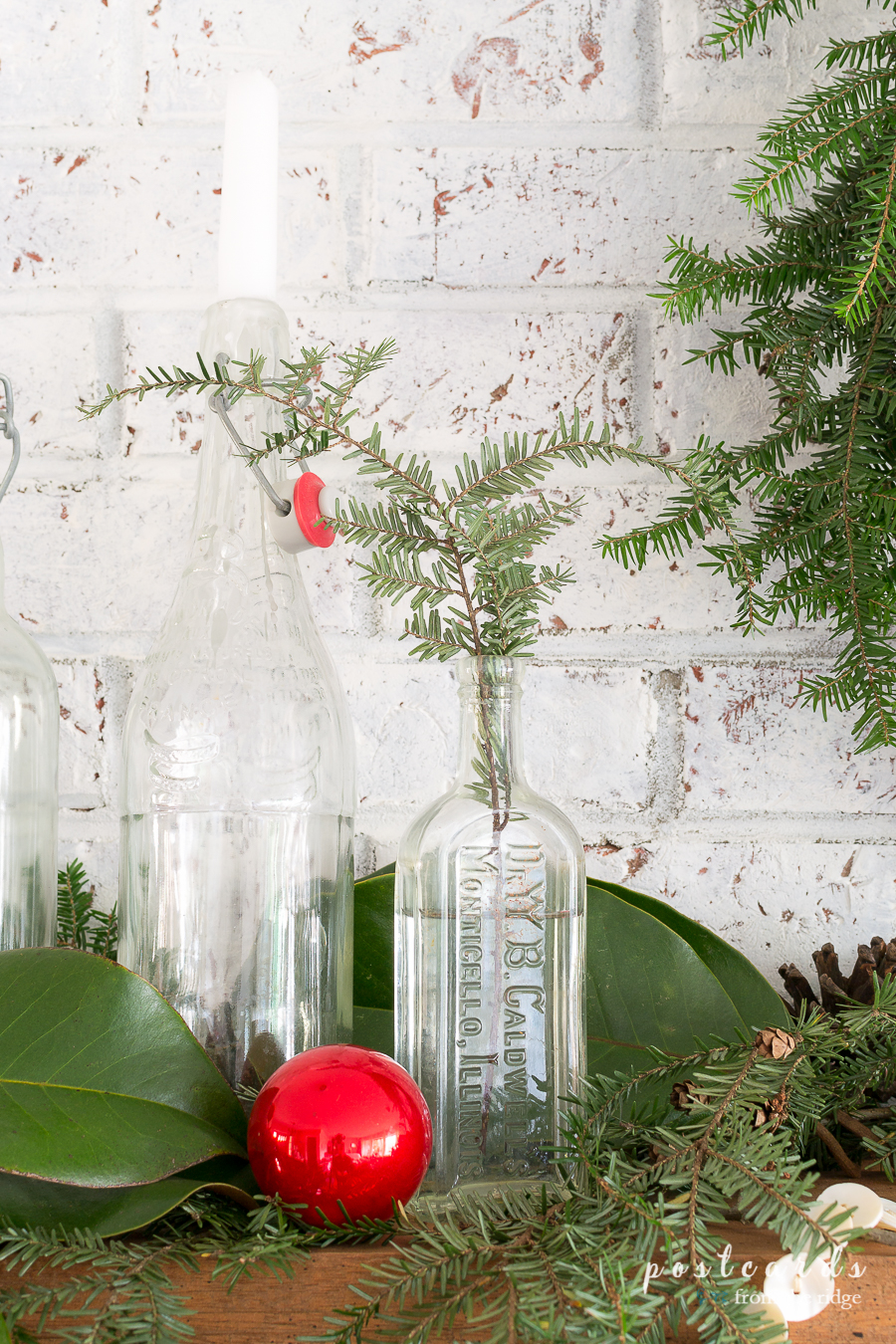 vintage glass bottles with candles and hemlock branches