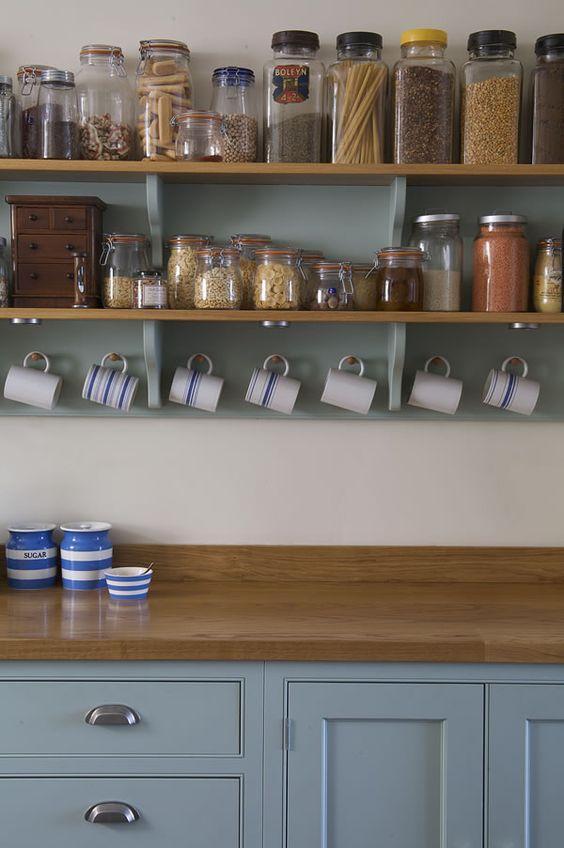 prateleira com mantimentos expostos e xícaras penduradas