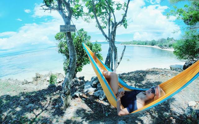 foto nyantai di pinggir pantai dengan hammock
