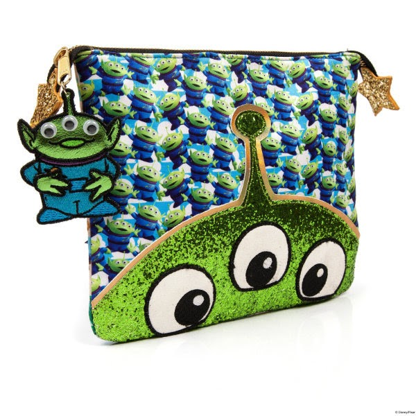 clutch bag sitting at angle with alien printed material and green glitter alien face at base of bag