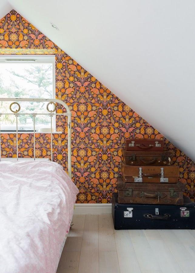 dormitorio con papel pintado y maletas apiladas decorando.