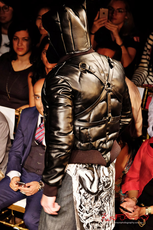 Black leather bondage strap style jacket and hood, reminiscent of Batman as seen from behind. Dexter Simmons at Art Hearts Fashion NYFW 2017 photographed by Kent Johnson.