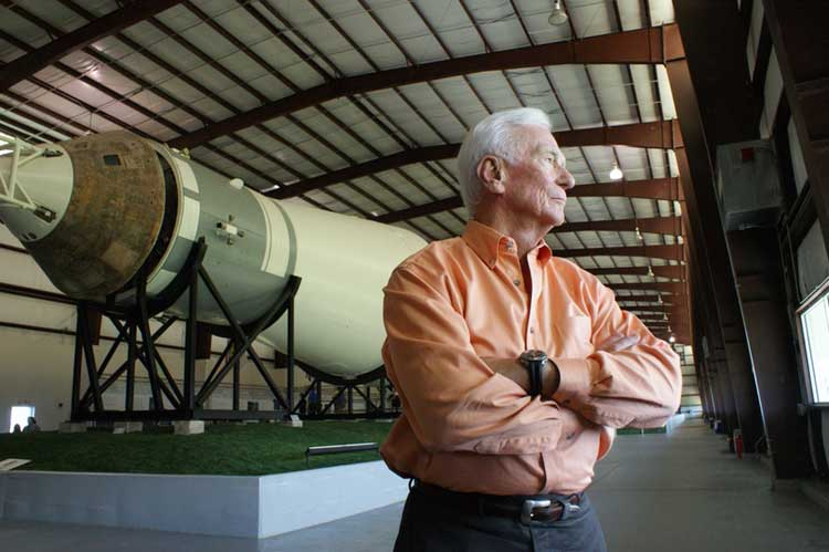 Astronaut Gene Cernan stands near a large rocket in Last Man on the Moon.