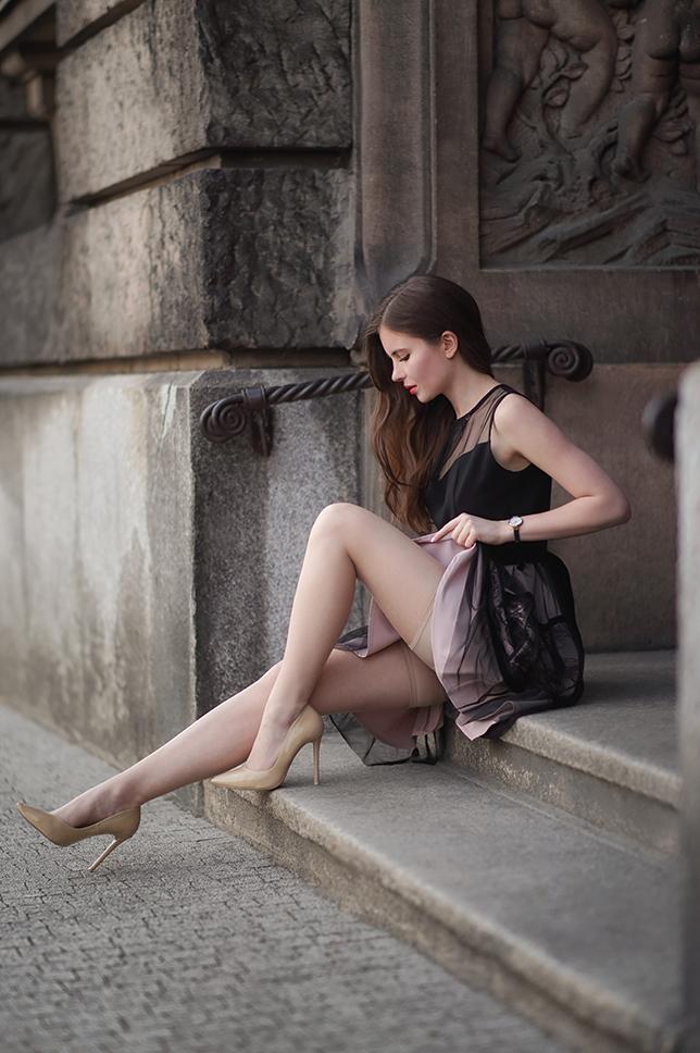 Czarna koronkowa sukienka, cieliste pończochy i beżowe lakierowane szpilki