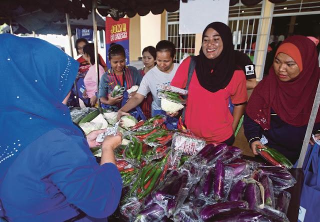 Pengunjung menggunakan kupon RM20 untuk mendapatkan barangan keperluan harian di Program Jom Pi Pasar DBKL