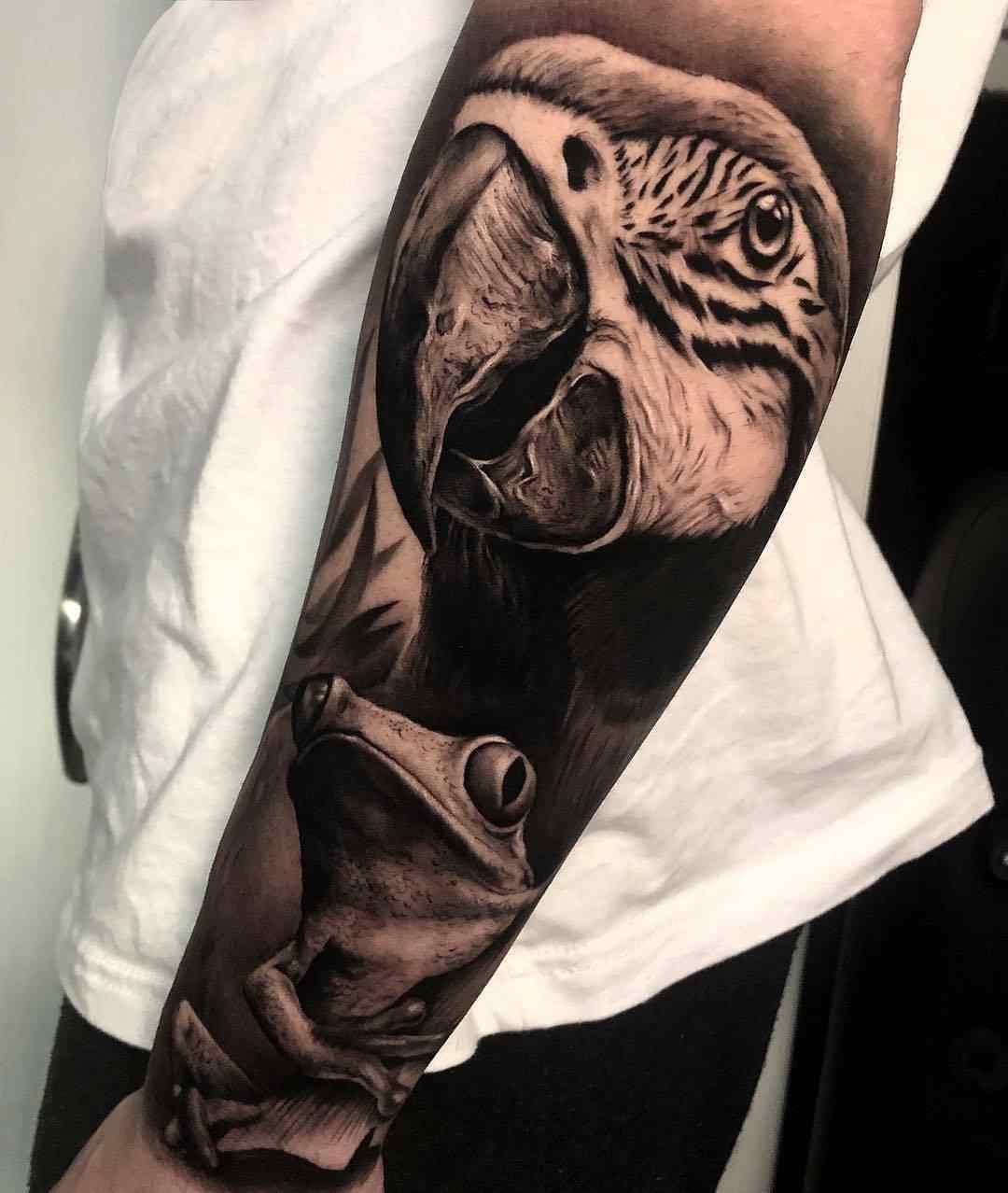 Vemos un tatuaje en blanco y negro de loro y rana