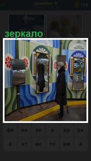 в комнате перед зеркалом женщина меряет пальто