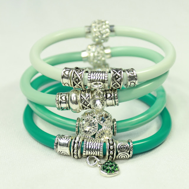 Stack of 4 resin bangles in shades of green, embellished with crystals and silver beads, finished with a sparkly magnetic clasp.