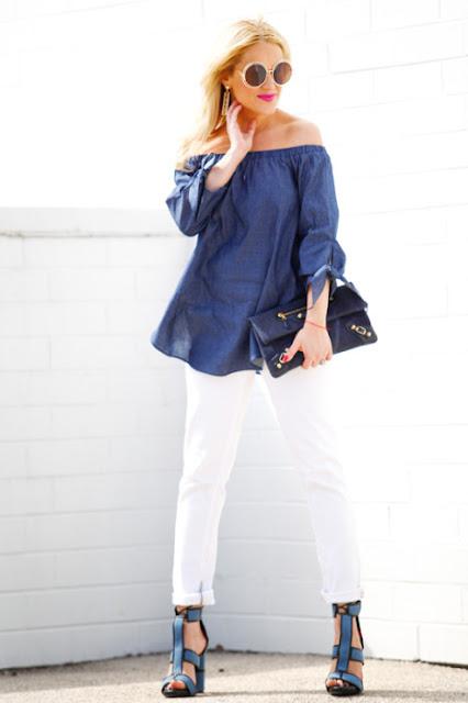 Беременная женщина в белых брюках и синем свободном топе с открытыми плечами