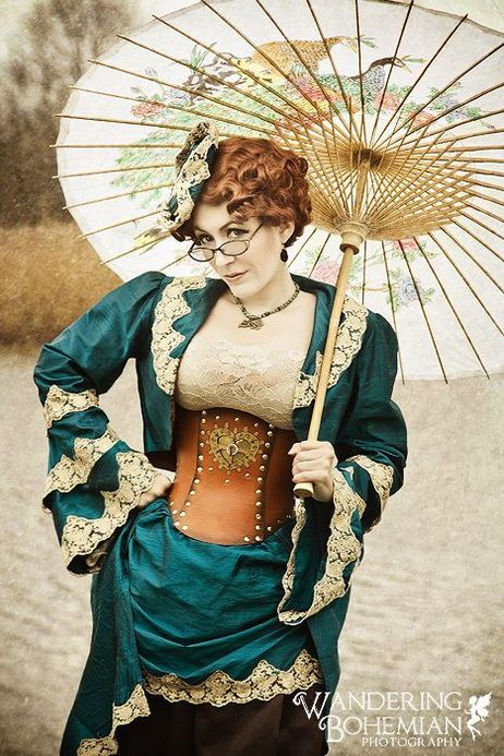 Woman in teal blue green 3 piece coordination steampunk costume with ivory off white lace trim. Matching jacket, skirt and hat. Brown leather studded underbust corset with gear heart. Eyeglasses, necklace and victorian paper parasol