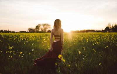 Chica rubia con vestido rojo paseando por un campo lleno de flores amarillas