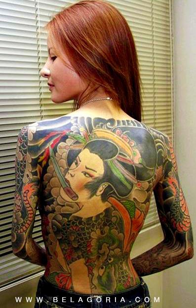 Vemos a una mujer peliroja posando de espaldas, tiene un tatuaje de geisha