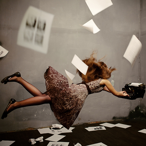Surreal image of a young woman floating in space writing on a typewriter.  Images and papers floating around space.