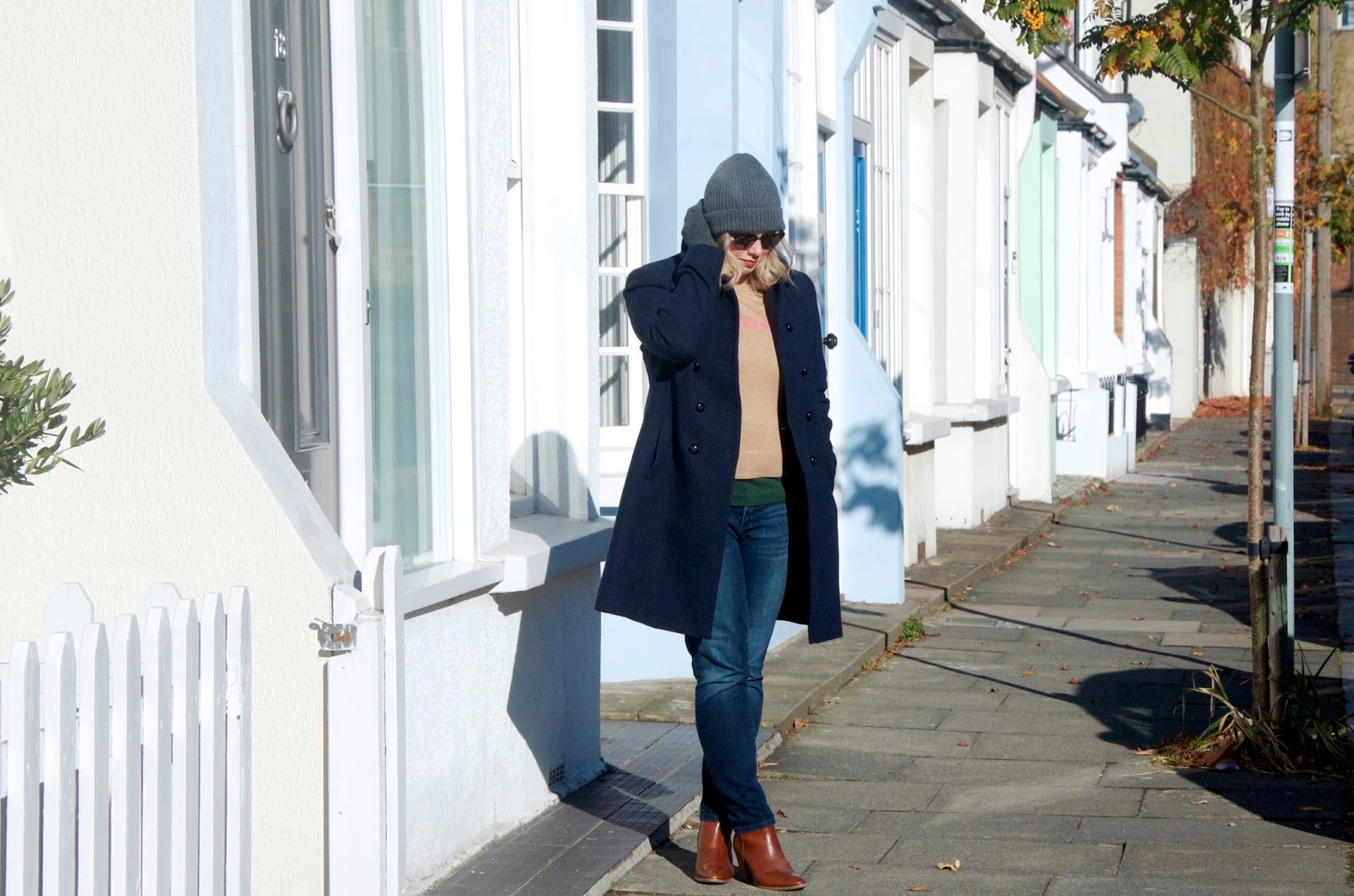 Grey hat, navy coat, camel sweater, jeans and brown boots with colorful houses and sidewalk