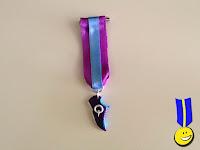 Foto de una medalla de fimo con forma de zapatilla de correr